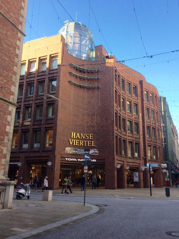 Das Eckgrundstück Poststraße/Große Bleichen war zur Bauzeit noch belegt, daher gibt es hier keinen mittigen Haupteingang, sondern nur zwei seitliche Eingänge.